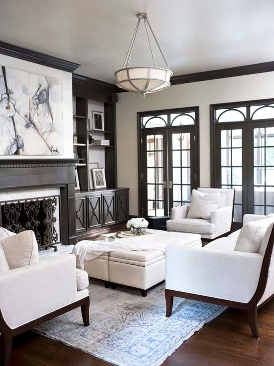 chic, elegant living room with taupe molding, taupe built-ins flanking fireplace, canvas art, wall of French doors & transom windows, cream cube tufted ottomans and white sofa & chairs with espresso wood frames (Linda McDougald Design)
