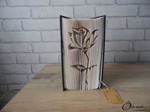 La collection A Livre Ouvert est une série de livres doccasion transformés en objets de décoration via plusieurs techniques (découpage, pliage ou décou-pliage). Chaque page est découpée et/ou pliée à la main pour donner vie à un motif.  Le modèle Rose est un livre découpé et plié pour représenter une jolie rose. Le livre possède une magnifique couverture bleue et or. VENDU SEUL