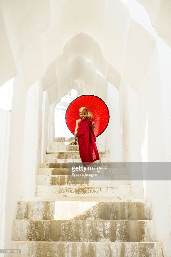 Little Asian Buddhist monk on staircase at Hsinbyume Pagoda, in Mandalay, Sagaing of Myanmar