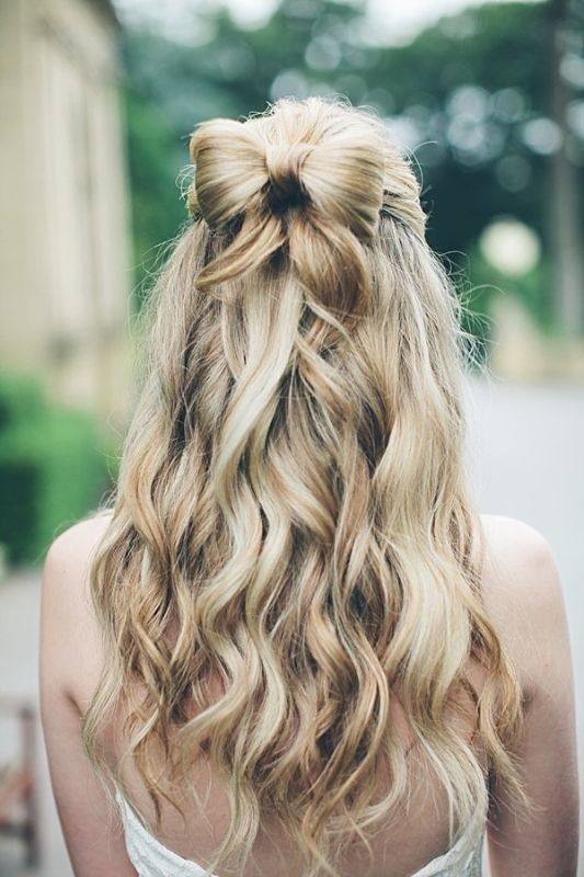 long loose waves and a sweet hair bow for the bride