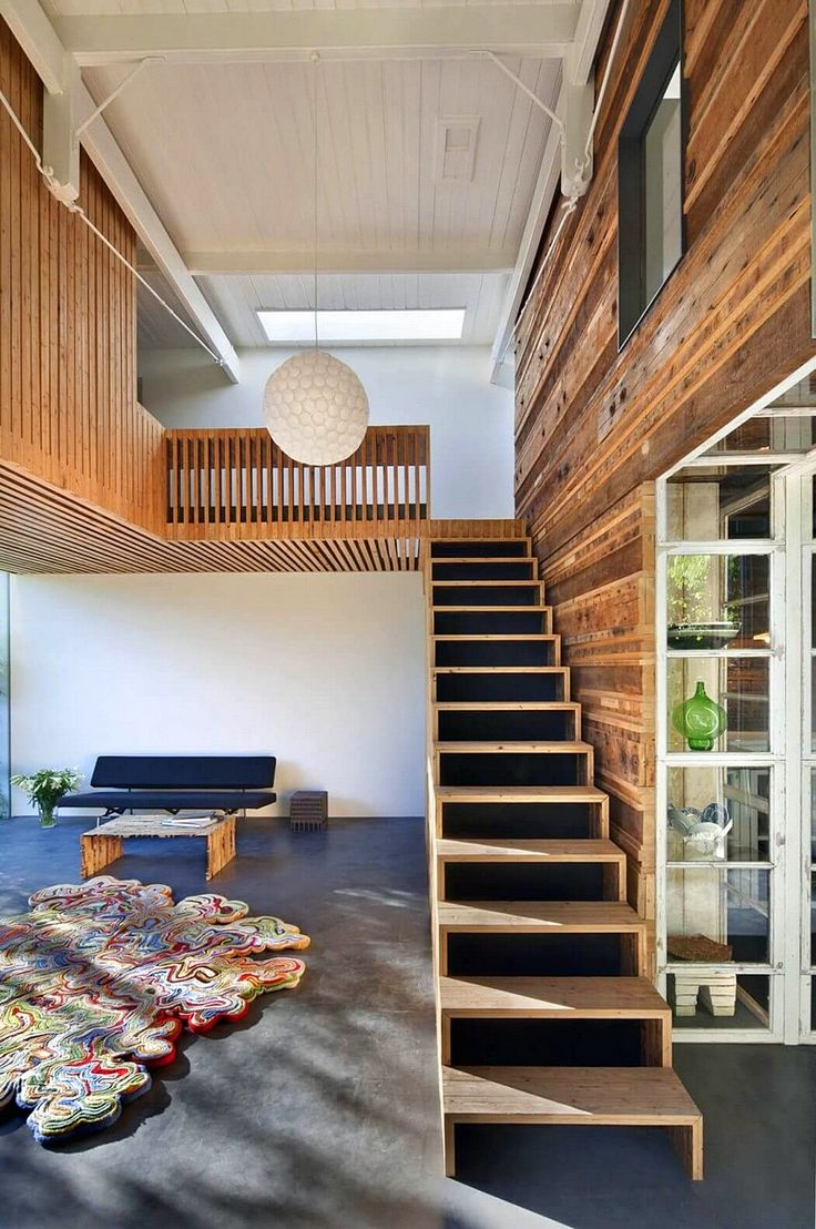 Wooden stairs lead you to the upper floor of this uniquely designed and  renovated coach house.