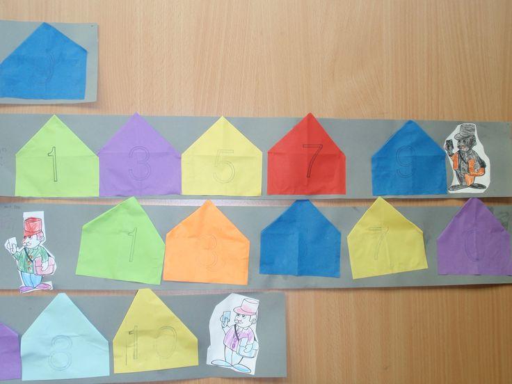 Huisjes vouwen met huisnummers erop gestempeld en postbode erbij.