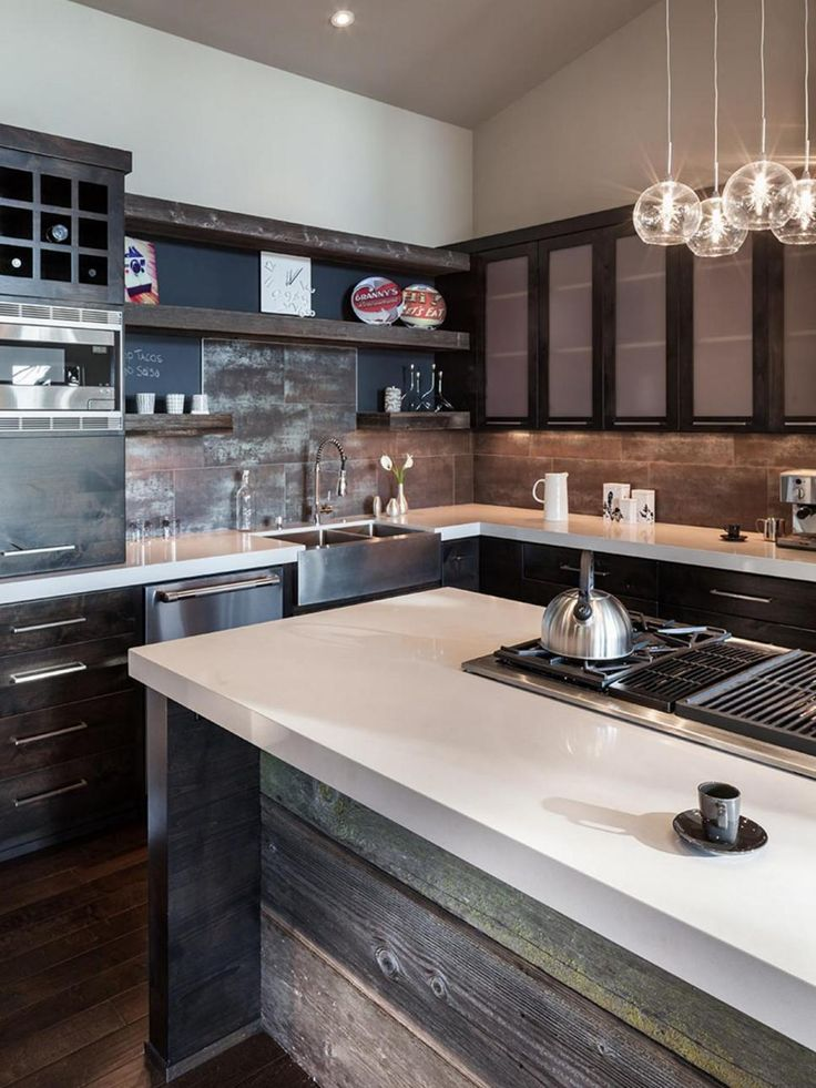 Glass pendant lights hang over a rustic wood island in this industrial kitchen. The gray tile backsplash and modern stainless steel appliances create a clean, stylish feel that is a signature of contemporary design.