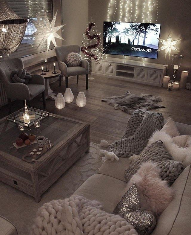 Such a beautiful home. A couch filled with pillows, a cozy home, and glittering lights!