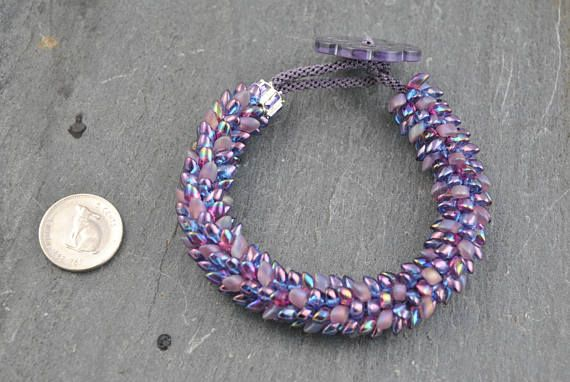 Purple Dragon Scales Kumihimo Artisan Bracelet #bracelet #kumihimo #kumihimobracelet #artisan #artisanbracelet #handmade #knotted #handknotted #woven #oneofakind #scale #dragon #dragonscale #magatama #magatamabeads #iridescent #frosted #mauve #lilac #amethyst #lightweight #flexible #feminine #showy