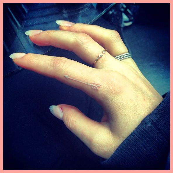 Ellie Goulding's white ink arrow finger tattoo