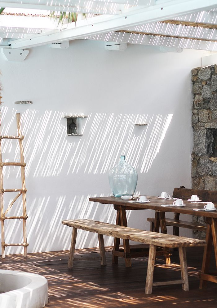 Rustic Outdoor Dining with white walls, raw wooden bench and table with roof racks. Mykonos / San Giorgio Hotel / exterior