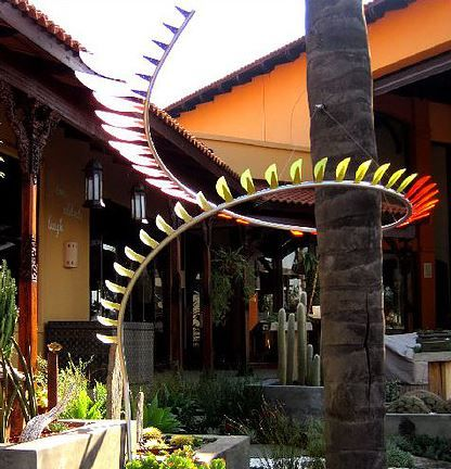 Custom  made , rolled steel and perspex spiral, wrapped around a tall palm tree, connecting ground level to sky
