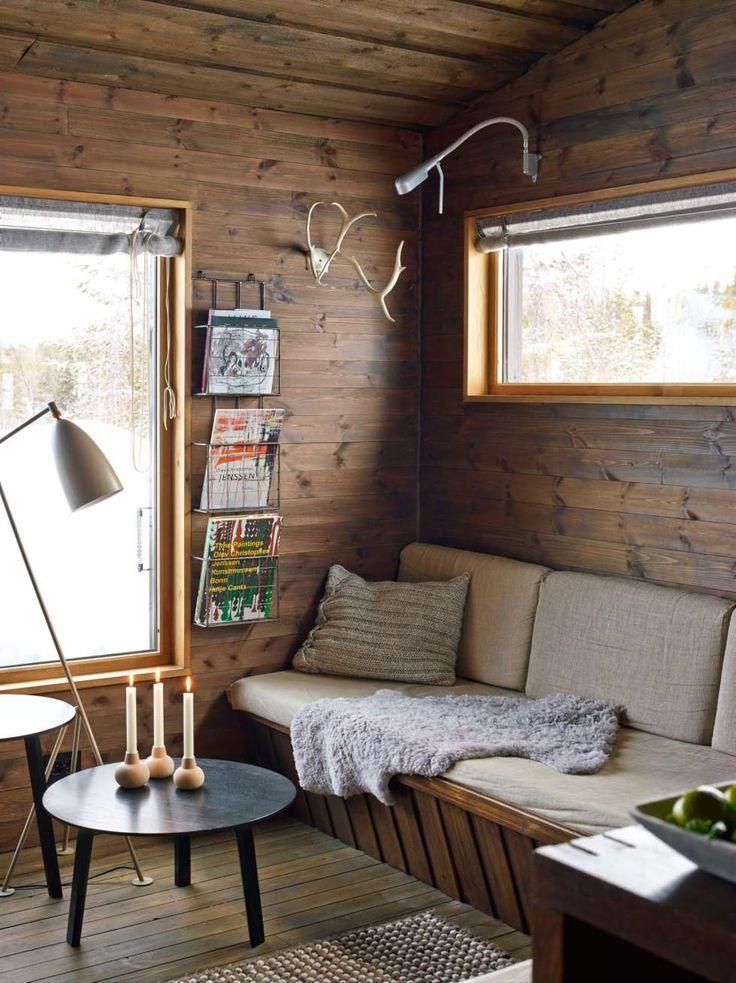 Lunt og lyst: Vinduet er plassert høyt over sofabenken for å danne en lun krok mot det store vinduet. Puten har Ellen strikket av restgarn. Geviret fulgte med hytta. Lampe, bord og matte fra Hay. Sofaen er trukket med linstoff.