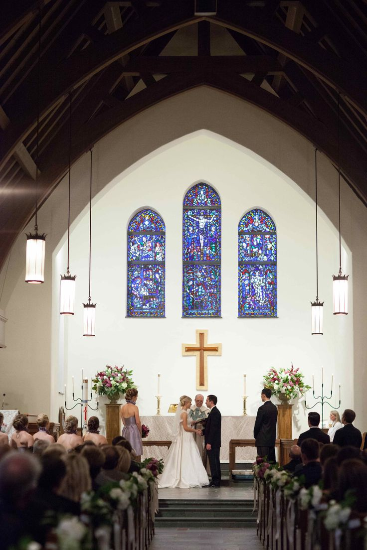 the couple exchanges their vows in a historic chapel adorned with two large and lush altar arrangements of purple, lavender, burgundy and white.