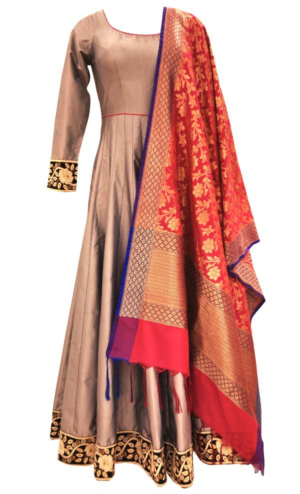 This set features a grey fully flared and pleated floor length suit in silk base with resham thread embellished border around the hem and cuffs. It also features a sheer back and hot pink dori tie up with metallic silver tasseled hangings. The contrast banarasi silk dupatta truly enhances the beauty of the outfit. It comes with a matching churidar pants. Get your hands on this magnificent creation and look utterly elegant.  Note: The design of the banarasi dupatta may change based…