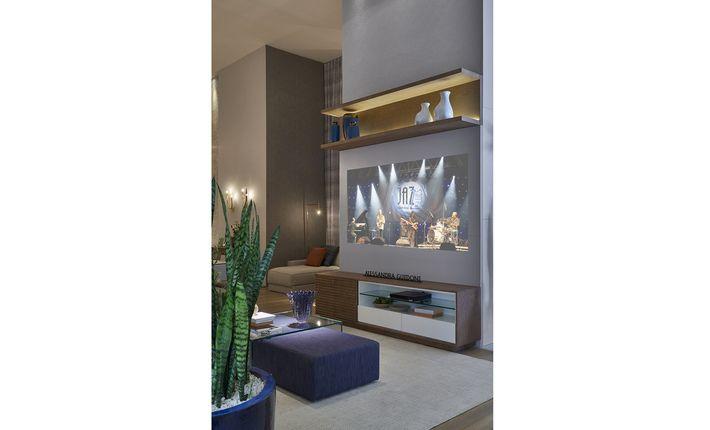 Inspirando-se em uma família moderna e contemporânea, a arquiteta e urbanista Alessandra Guidoni criou o espaço home theater e sala de jantar. Linhas retas e tons claros no mobiliário, mesclados com cores mais escuras na decoração, caracterizam o ambiente. As luminárias, na tonalidade cobre, dão o toque de modernidade ao espaço, e o papel de parede confere sutileza. O diferencial do espaço está na disposição dos móveis e na iluminação, que destaca os elementos da decoração.