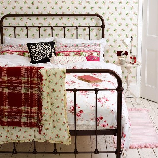 Pretty vintage bedroom ||| This period-style iron bed has been softened with floral soft furnishings in a mix of ditsy patterns. The dainty wallpaper creates a delicate backdrop.(Wallpaper: Cath Kidston)