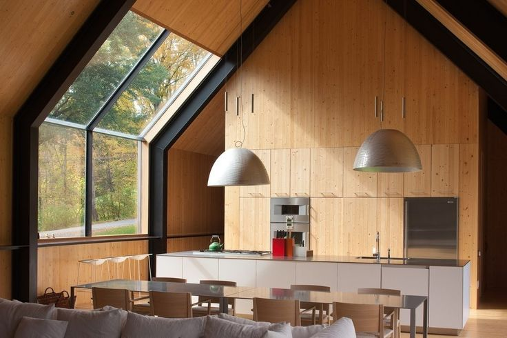 This modern gable Vermont home has an all wood interior with wood cabinetry, white glossy kitchen island, exposed black steel structure and oversized hanging lights.