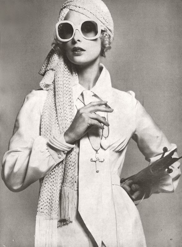 Ladylike white silk shirtdress by Salvador. Coffee coloured goatskin bag from Harrods. Pure silk lace jersey scarfed turban by Frederick White sunglasses by Oliver Goldsmith. Ivory heart and ivory and gold cross on chains by Ken Lane.  Photo by Clive Arrowsmith. Harpers and Queen, February 1975