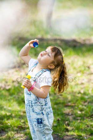 Скачать - Маленькая девочка надувает мыльные пузыри — стоковое изображение #106755160