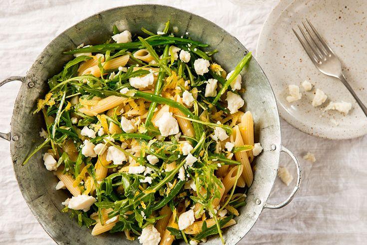 Keitä pasta ohjeen mukaan, lisää pavut viimeiseksi kahdeksi minuutiksi ja valuta kun molemmat ovat kypsiä. Hienonna shalottisipuli ja valkosipulinkynsi ja sekoita kastikkeen ainekset keskenään. Viipaloi kevätsipulit ja murenna vuohenjuusto. Sekoita pasta, pavut, kastike, kevätsipulit ja rucola. Raasta päälle sitruunankuori ja ripottele pinnalle vuohenjuusto.