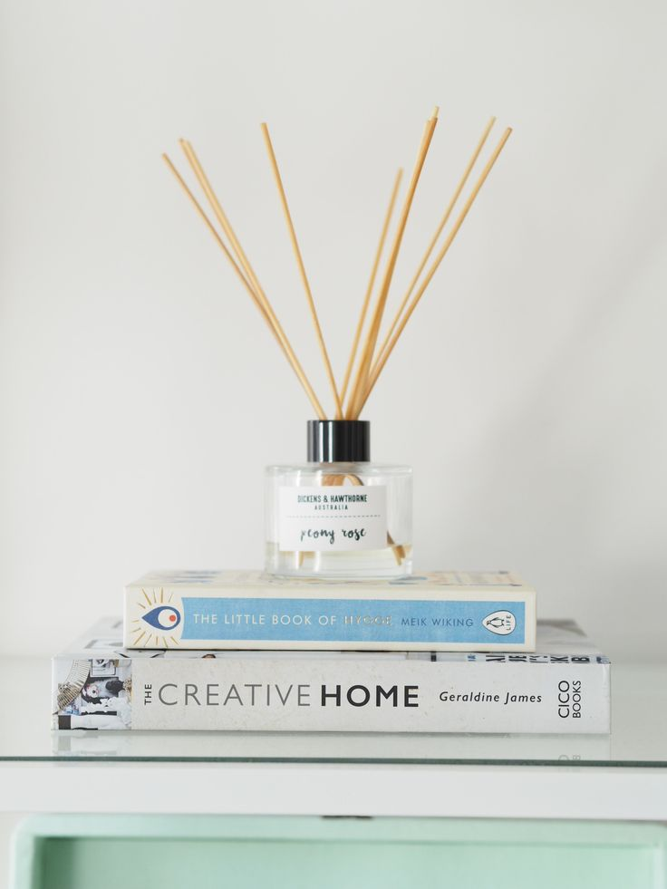 Books and reed diffuser on bookcase