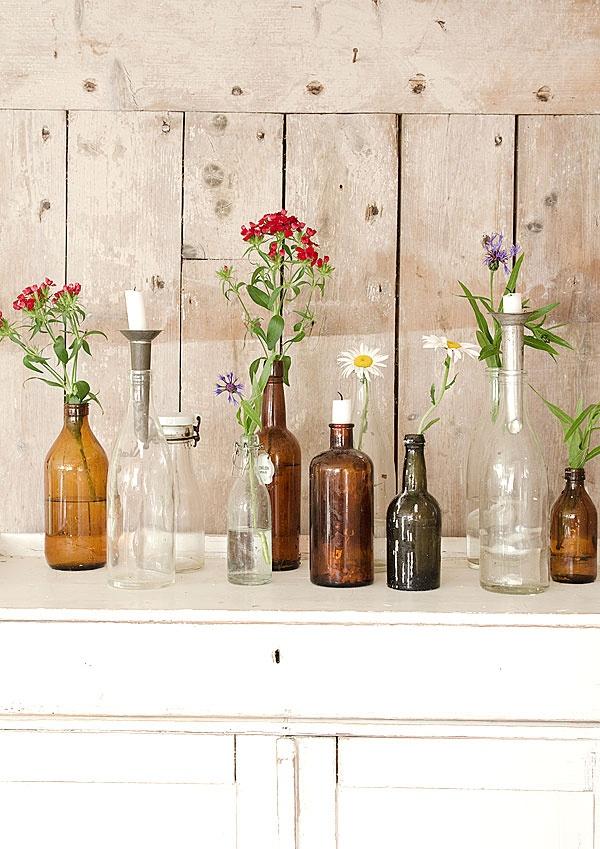 Dekorera med midsommarblommor i flaskor.