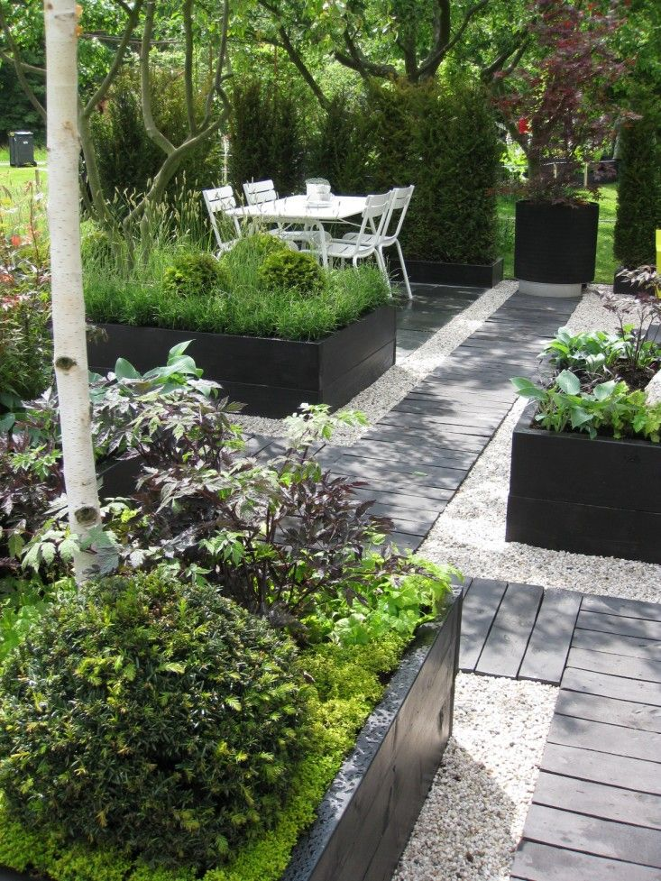 I love the dark raised beds, pebble edges and wood plank path. Very clean and modern while still being very functional.