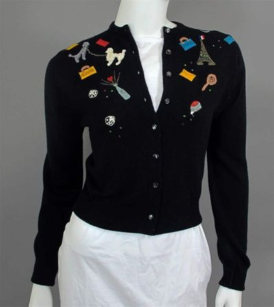 Elsa Schiaparelli vintage 1950's embroidered black cashmere cardigan sweater in a classic style with eight pearlized black button closure, ribbed round collar, ribbed cuffs and hem. Embroidery features French travel icons: poodles, travel bags, the Eiffel Tower, tennis, champagne, mirror and envelopes with red, green and blue rhinestones.