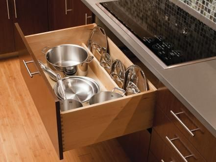 Keep pots handy for cooking by storing them right below the range. This convenient drawer even features a partition at the back that neatly stores all the lids in plain view. Photo courtesy of Dura Supreme Cabinetry