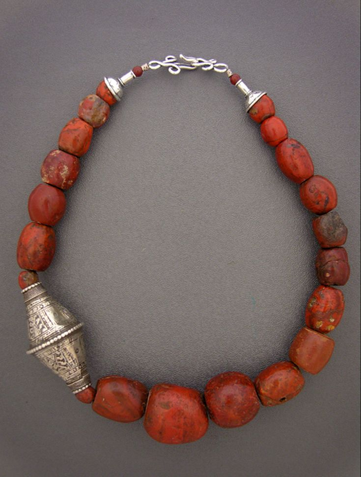 By Anna Holland | Necklace; fabulous incredibly old jasper, possibly ancient, from West Africa. Combined with a very large and beautiful antique Baluch bead from the inhabitants of Baluchistan, currently including parts of Iraq, Afghanistan, and Pakistan. Sterling silver cones and hook and eye clasp. | Sold