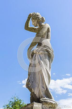 Medieval stone draped woman statue over blue sunny sky in the garden of Peles castle, Sinaia, Romania.