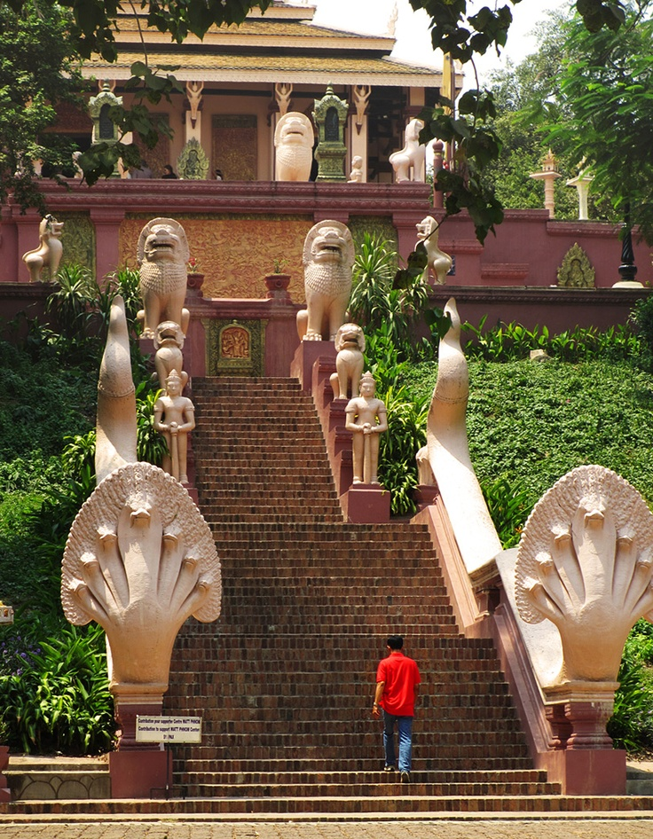 Wat Phnom Steps:  A local worshipper begins to ascend the grand eastern staircase, leading to the famous Wat Phnom. Stone lion statues and naga (snake) balustrades guard the temple.   ----  www.tropicalasiatravel.com