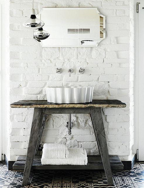 Great idea for a beach house. Exposed brick painted white and an old wooden plaque used as the foundation for the sink