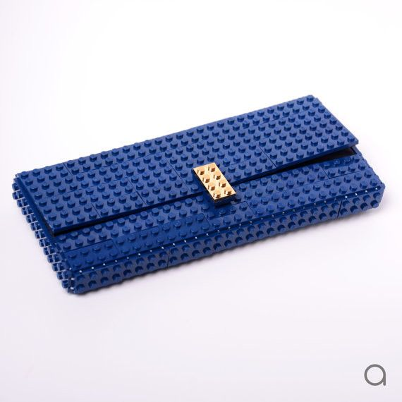 Elevate evening looks with this black or dark blue AGABAG clutch. It has gold plated elements made entirely with LEGO bricks. Style yours with a dress, filling it with your smartphone, lipstick and cards.