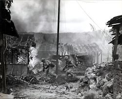 U.S. Marine infantrymen move quickly to take up new positions against Japanese troops during the Battle of Saipan, while the village of Gara...