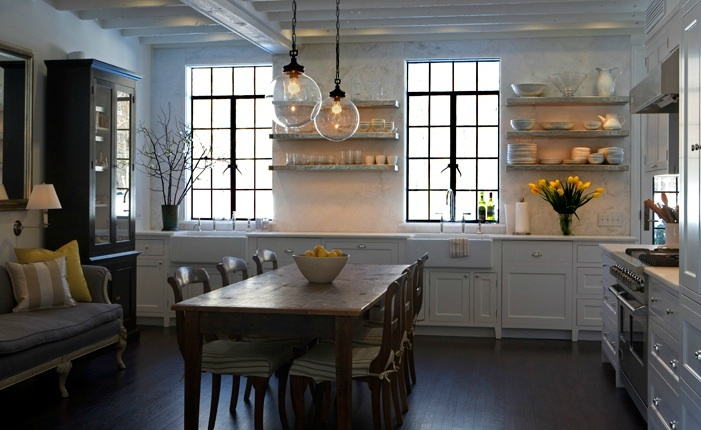 L shaped kitchen design with Arteriors Reeves Pendants in Antique Brass, white kitchen cabinets with marble slab countertops & backsplash, marble floating shelves, farmhouse sink, rustic wood dining table & chairs.