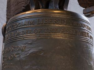 """Color photo showing a detail of the Liberty Bell, focusing on the words """"Proclaim LIBERTY"""" near the top of the bell."""
