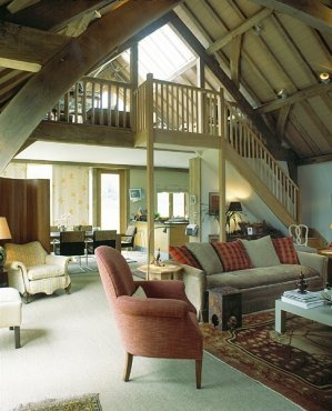 Gallery with staircase overlooking barn room. By Roderick James Architects.