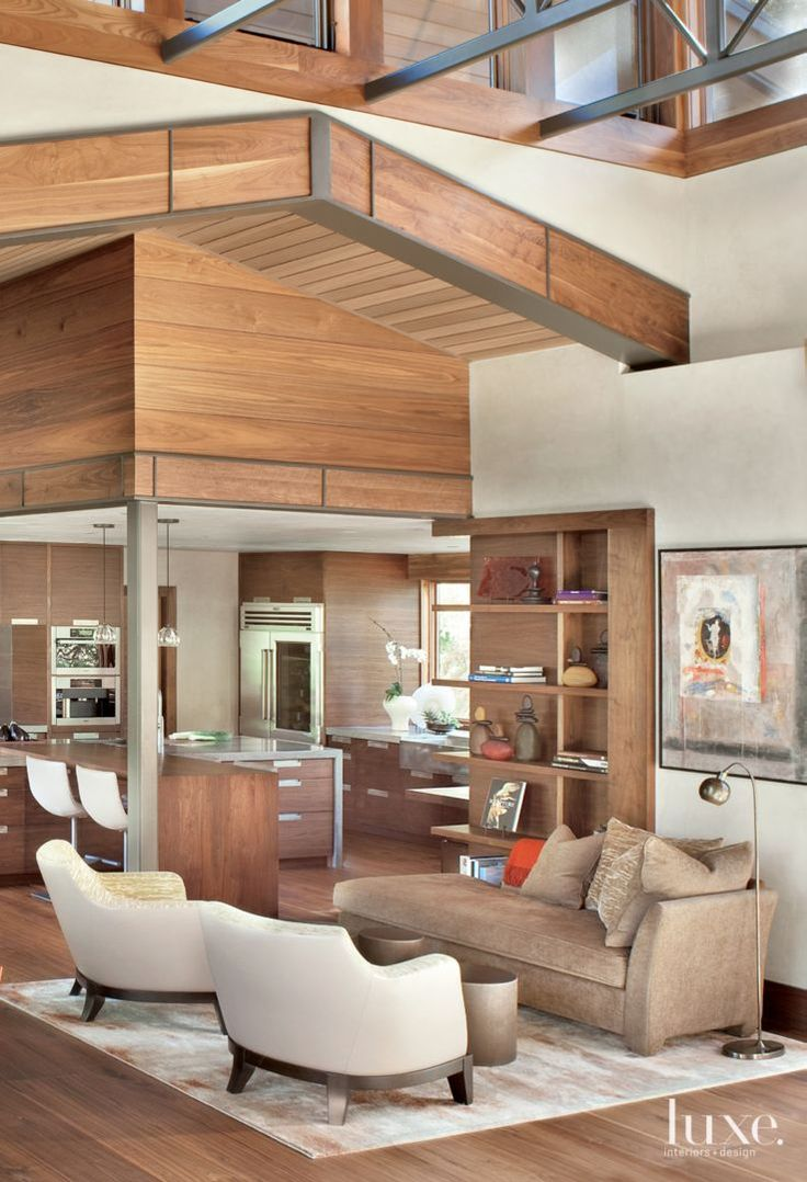 Contemporary exposed steel beams appear less industrial in this living room by added wooden inserts | LUXE Source