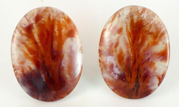 Here is a matching pair of old stock cabochons of Flame Agate from Chihuahua, Mexico. They are a standard 40 mm x 30 mm and are 4 mm thick. There is a rounded bezel of approximately 1.5 mm to help with its setting in a custom piece of jewellery. The back has been polished.  An old