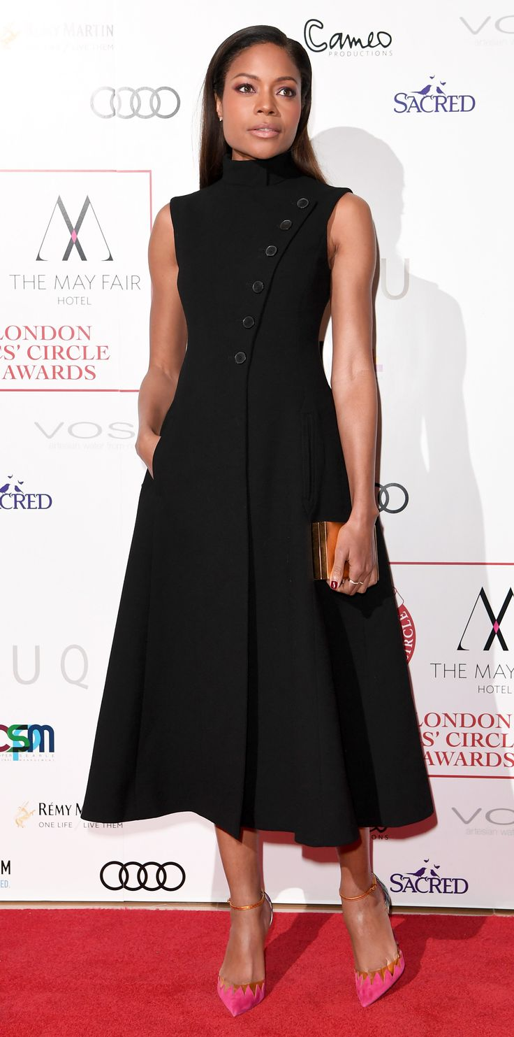 Look of the Day - Naomie Harris: For the London Critics' Circle Film Awards Naomie Harris let her accessories- a gold Lee Savage clutch and hot pink suede pumps- pop against her black asymmetric- buttoned vest dress by Dior.