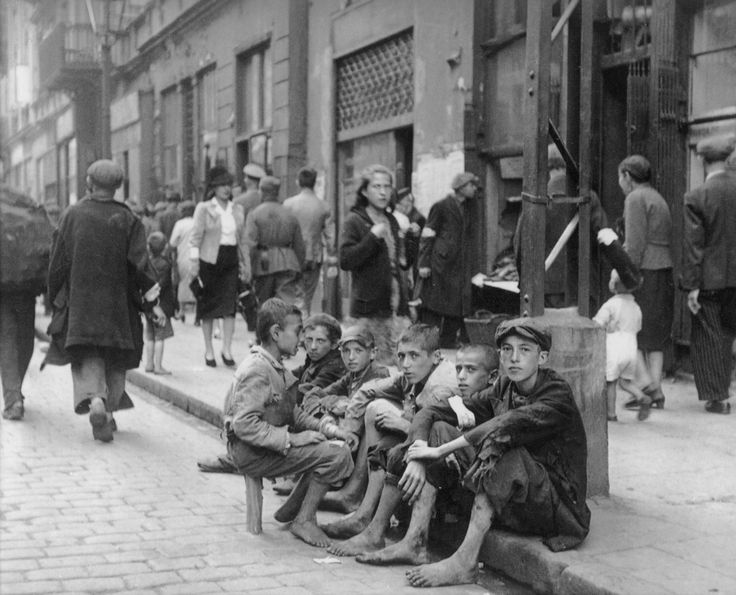 Jewish children sit barefoot and in ragged clothing in Nowolipie Street in the Warsaw Ghetto. The Warsaw Ghetto was the largest of all Jewish ghettos established by the Germans during the war. It was established in the Polish capital between October and November 1940, in the territory of the General Government of German-occupied Poland, with over 400,000 Jews from the vicinity forced to reside in an area of 3.4 km2 (1.3 sq mi). The Germans closed the Warsaw Ghetto to the outside world on 16…