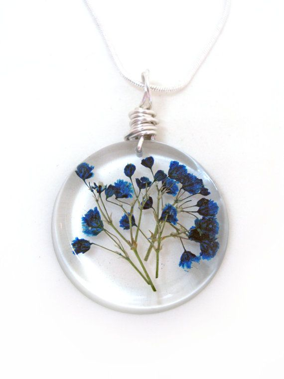 This listing is for a lovely pendant of several blue babys breath pressed flowers encased in jewelers grade resin. The pendant is a disc…