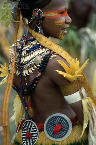 A woman from the Mekeo tribe wears an elaborate ceremonial feather costume and body paint. Gulf of Papua, Papua New Guinea. | | © Charles & Josette Lenars
