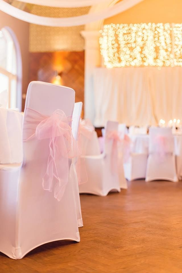 Stretch white chair cover with baby pink organza sash. Perfect for weddings, birthdays and christenings.