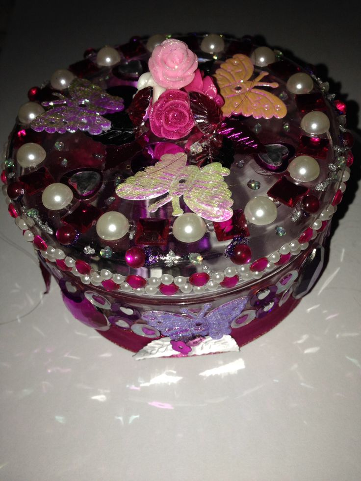 A recycled glass jar covered in bling becomes a pretty trinket jar.  I used rhinestones, pearls, sequins, fabric and sequin butterflies.  The roses on the lid form a handle and we're originally earrings.