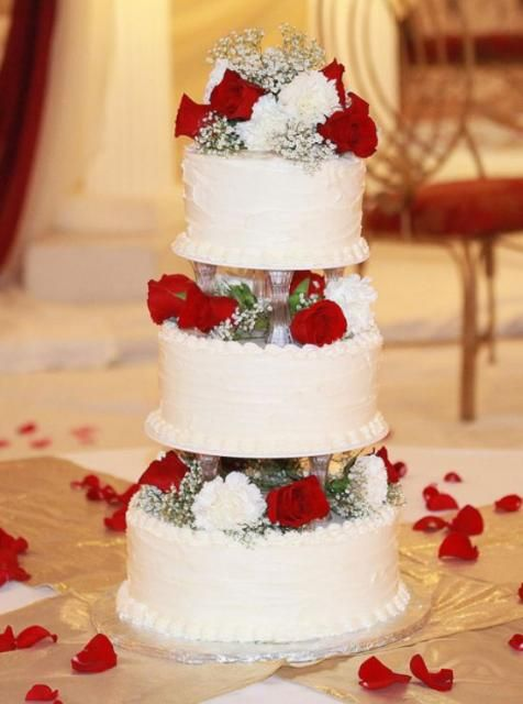 3 tier round white wedding cake with red roses and stands between each tier and rose petals around cake.JPG