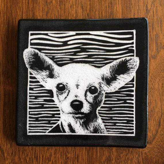 Handmade Tile. Porcelain clay with black slip and clear glaze.  This 6.25inx6.25inx.5in tile is a hand-carved portrait of Dolly, an adorable chihuahua mix recently adopted from the Seattle Humane Society. This tile can be installed in a field of commercial tiles, hung on a wall (hardware available upon request), or used as a trivet. It's the perfect gift for your favorite pet lover. For every shelter dog tile sold, $5 will go to the Seattle Humane Society.