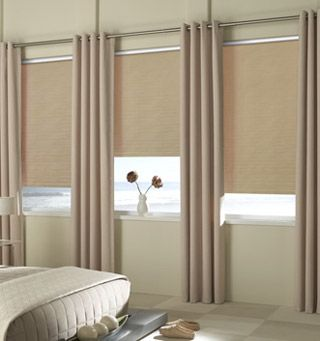 Stationary grommet drapes paired with roller shades are trending now!