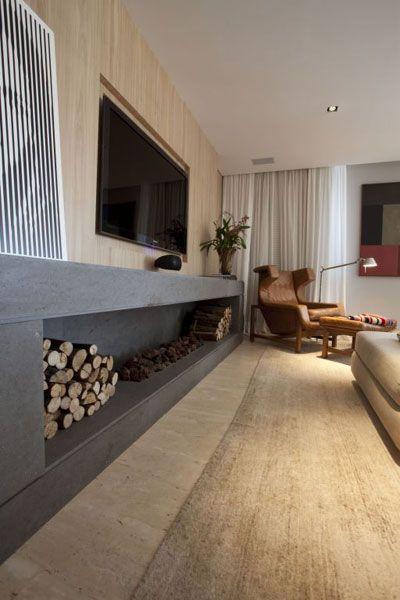O painel em madeira freijó lavado tem TV acoplada e logo abaixo uma lareira em tom de cinza.
