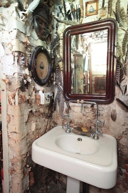 Portia Munson recobriu as paredes do banheiro com pedaços de casca de árvore. O ambiente ainda ganhou penas, fotografias antigas e elementos étnicos de madeira