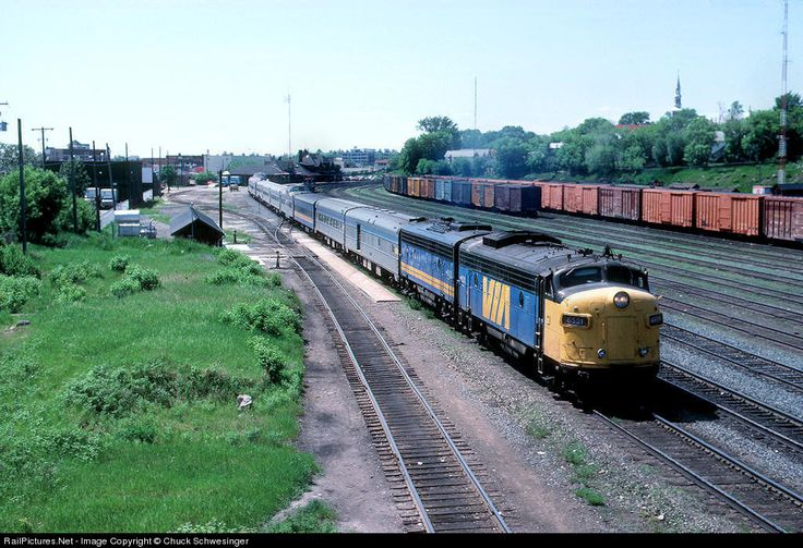 VIA 6531,6632 are starting to accelerate train 2 away from the station stop in Kenora on a humid late May afternoon. In the distance you can see the CPR station,freight house and the local SW series unit assigned to the yard. May 1987
