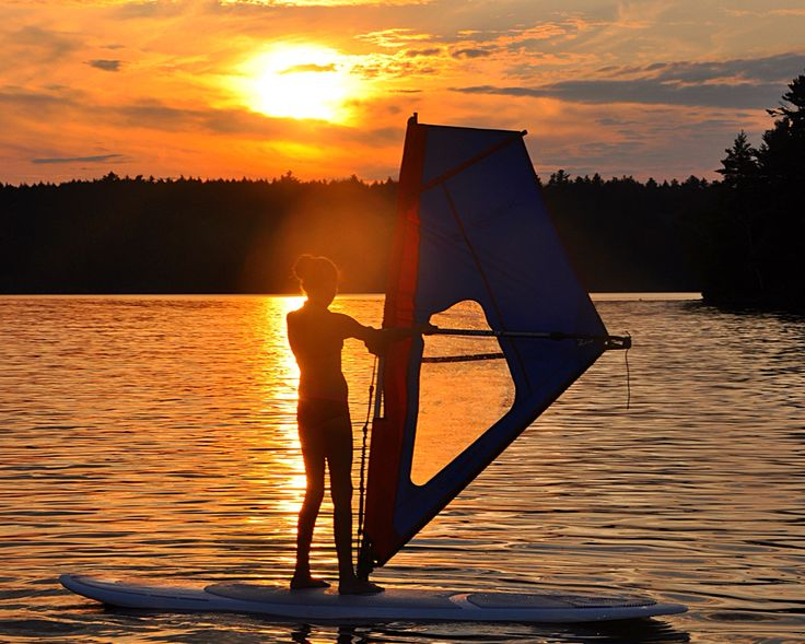 Caroline windsurfing on the sunset lit lake. Beautiful evening at the cottage. #WorkPlayCare #WorkSmart #PlayHard #CARE #Cottage #SunSet #WindSurf